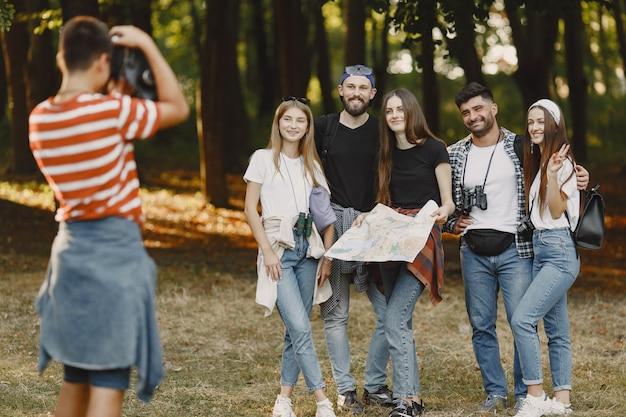 冒険、ハイキング、人々のコンセプト。森の中の笑顔の友達のグループ。男は写真を撮ります。