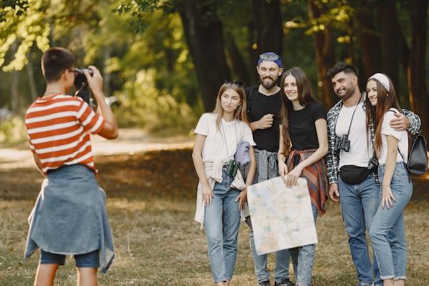 Концепция приключений, походов и людей. группа улыбающихся друзей в лесу. парень сфотографируй.