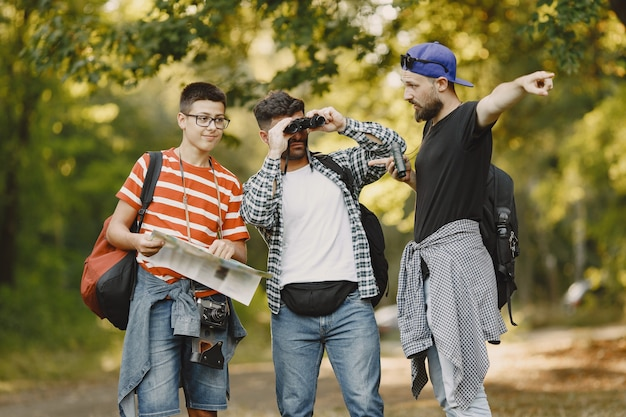 모험, 하이킹 및 사람들 개념. 숲에서 웃는 친구의 그룹입니다. 쌍안경을 가진 남자.