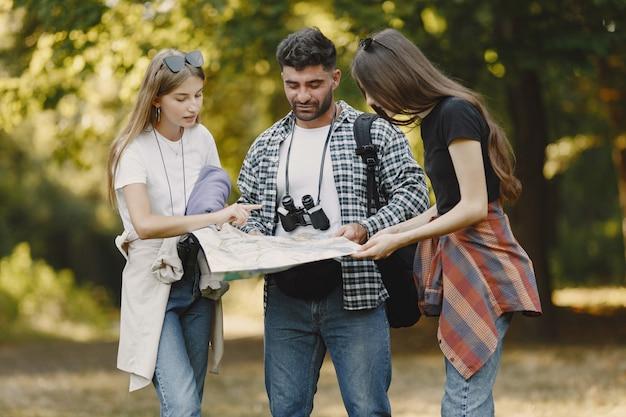 Концепция приключений, походов и людей. группа улыбающихся друзей в лесу. человек с биноклем. Бесплатные Фотографии