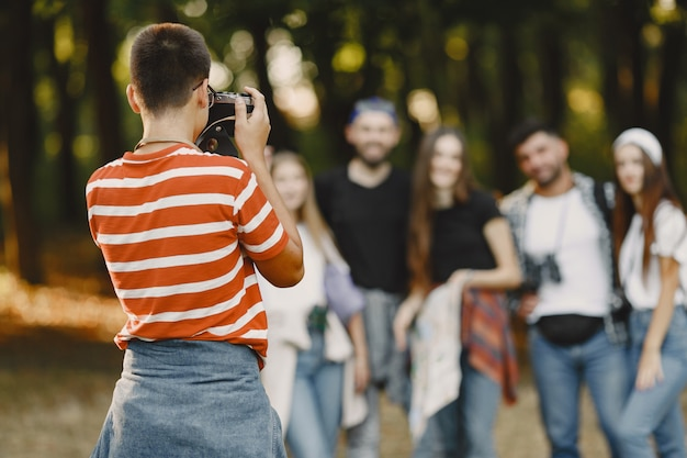 Adventure, hike and people concept. group of smiling friends in a forest. guy take a photo.