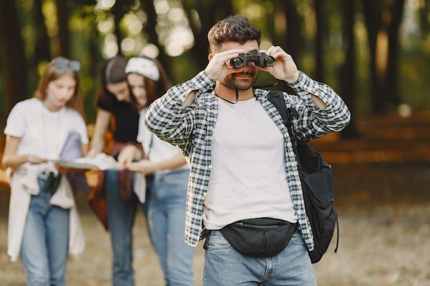 Concetto di avventura, escursione e persone. gruppo di amici sorridenti in una foresta. uomo con il binocolo.