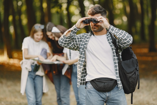 Adventure, hike and people concept. group of smiling friends in a forest. man with binoculars.