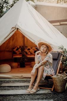 Приключение в таиланде. жизнерадостная и оптимистичная женщина-путешественница в своем путешествии по таиланду. молодая женщина позирует на стуле на фоне своего лагеря.