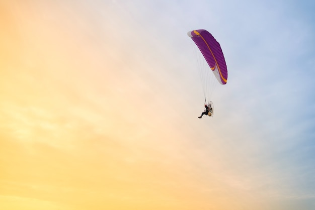 Adventure man active extreme sport pilot flying in sky with paramotor engine glider parach