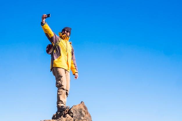 青い空と山の頂上に屋外で立っている冒険男