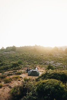 Adventure motorcyclist camping in wild