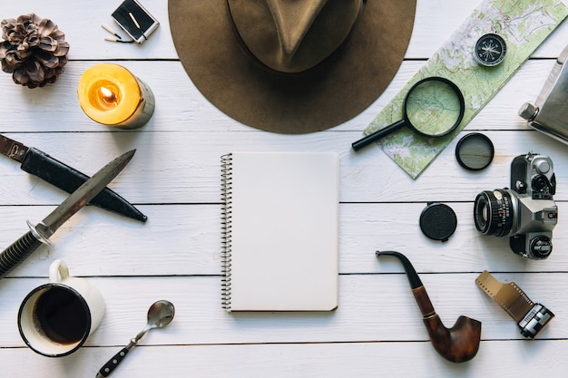 Adventure planning flat lay with travel vintage gear on white wooden table with hat and copy space