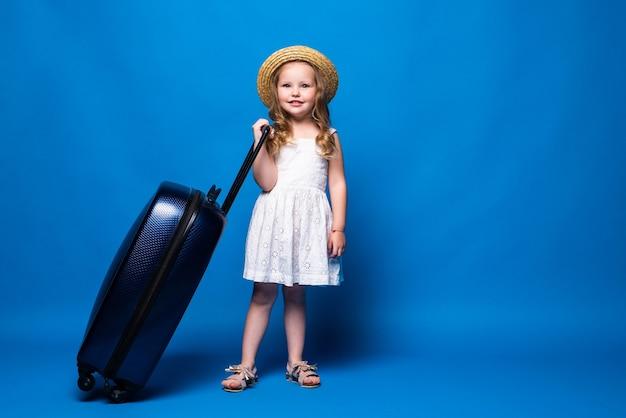 모험 여행 개념. 행복 한 아름 다운 귀여운 소녀 파란색 벽에 가방을 걷고있다