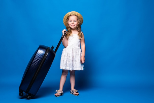Adventure travel concept. happy beautiful cute little girl is walking with a suitcase on blue wall