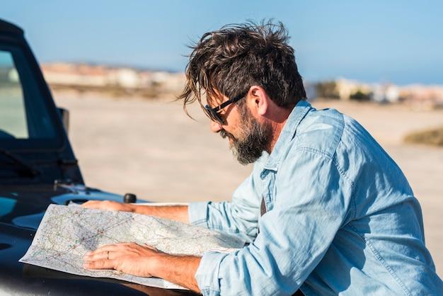 冒険旅行のライフスタイル-旅行と旅を計画するために紙の地図を探しているひげを生やした成人男性-目的地を選ぶ人々-放浪癖の生活と車の輸送