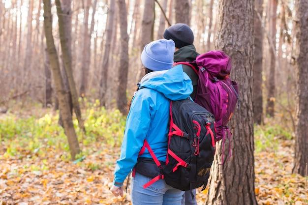 모험, 여행, 관광, 하이킹, 그리고 사람들의 개념 - 자연 배경 위에 배낭을 메고 걷는 부부의 뒷모습.