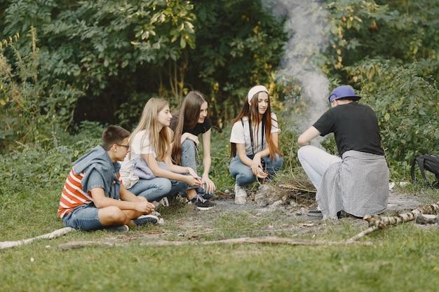 모험, 여행, 관광, 하이킹 및 사람들 개념. 숲에서 웃는 친구의 그룹입니다. 모닥불 근처에 앉아있는 사람들.