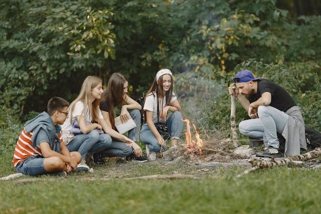 Концепция приключений, путешествий, туризма, походов и людей. группа улыбающихся друзей в лесу. люди сидят у костра.