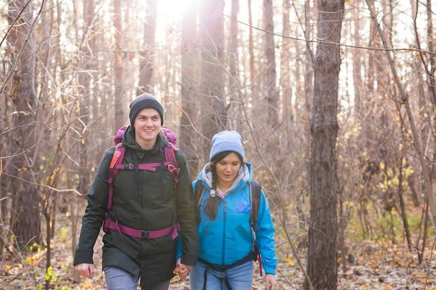 冒険、旅行、観光、ハイキング、人々のコンセプト-自然の風景の上をバックパックで歩く笑顔のカップル。