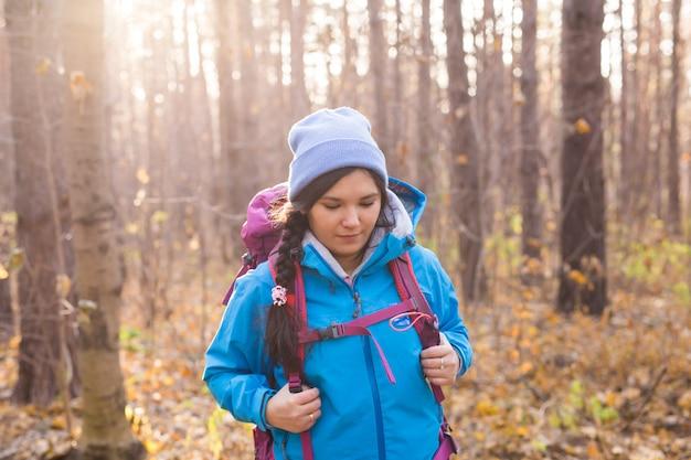 冒険、旅行、観光、ハイキング、人々のコンセプト-秋の自然の上をバックパックで歩く笑顔の観光客の女性。