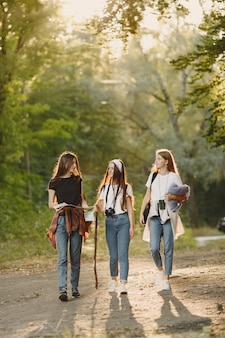 모험, 여행, 관광, 하이킹 및 사람들 개념. 숲에서 세 여자.