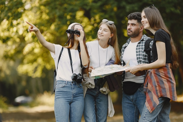 Avventura, viaggi, turismo, escursione e concetto di persone. gruppo di amici sorridenti in una foresta. uomo con il binocolo.