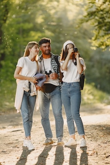Adventure, travel, tourism, hike and people concept. group of smiling friends in a forest.