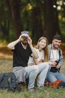 Avventura, viaggi, turismo, escursione e concetto di persone. gruppo di amici sorridenti in una foresta.