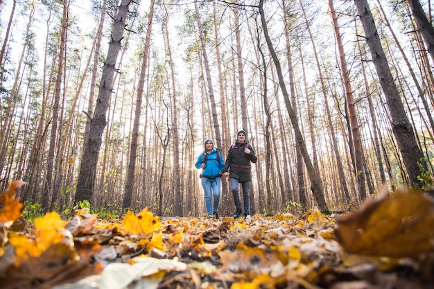 Adventure, travel, tourism, hike and people concept - smiling couple walking with backpacks over autumn natural background.