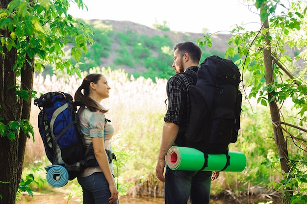 Adventure, travel, tourism, hike and people concept - smiling couple with backpacks outdoors.