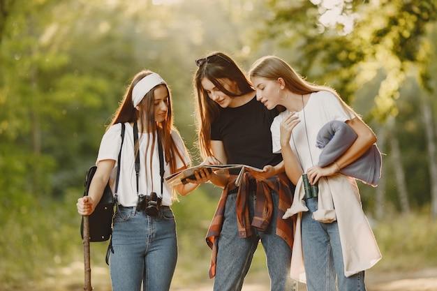 Avventura, viaggi, turismo, escursione e concetto di persone. tre ragazze in una foresta.