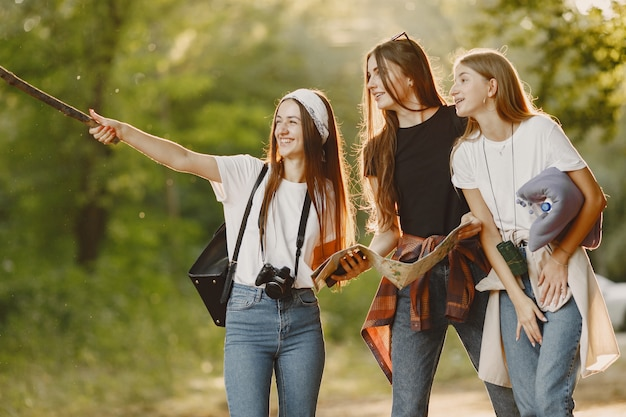 Adventure, travel, tourism, hike and people concept. three girls in a forest.