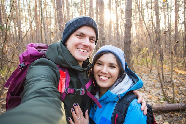 Adventure, travel, tourism, hike and people concept - tourists smiling couple taking selfie over trees