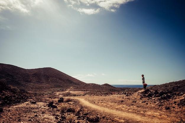 Приключенческий треккинг для стоящей женщины, наслаждающейся свободой и здоровым образом жизни - красивое живописное место с горами и морем.