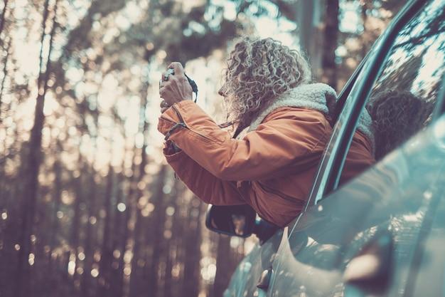 冒険休暇、休日、旅行、ロードトリップ、人々のコンセプト-森の森の自然に写真を撮る車の窓の外で幸せな笑顔の若い大人の女性または若い女性