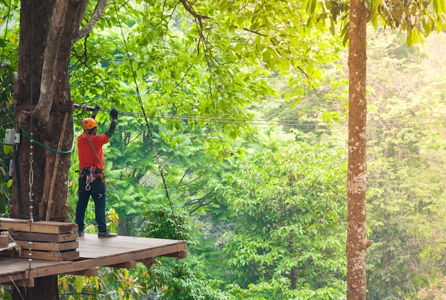 Adventure zipline high wire park - people on course in mountain helmet and safety equipment, ready to descend on zipline in forest, extreme sport