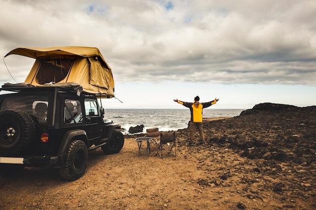 自由を楽しむためにオフロード車とルーフテントで旅をする冒険家の男と探検家のコンセプトは、自然の力の近くに住む世界を発見する海の海岸のホームビュー