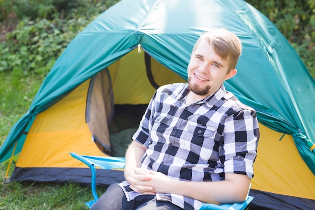 Приключения, походы, летний туризм и концепция природы - молодой человек сидит рядом в оранжевом палаточном лагере