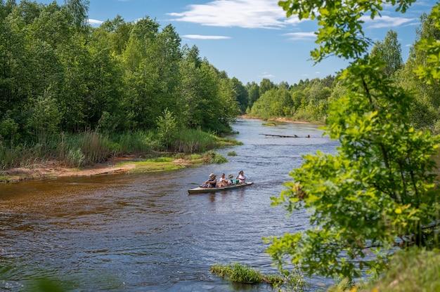 울창한 숲속의 아름다운 강에서 모험을 즐기는 친구들이 함께 카누를 타고 있습니다. 숲에서 아름 다운 강 아래로 카누. 여름에 강에서 카누 여행