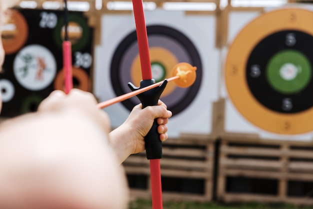 Adventurous child playing to throw arrows with a crossbow to a toy bullseye.