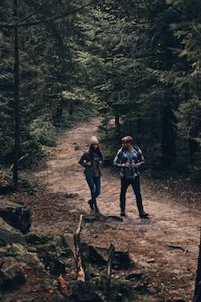 Пара приключений. полная длина красивой молодой пары, гуляющей вместе в лесу, наслаждаясь своим путешествием