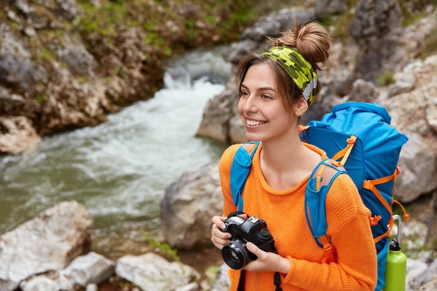 Adventurous female enjoys travel adventure, has hiking activity and nature tour, makes photo of landscapes, holds professional camera