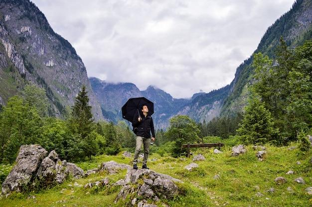 우산으로 바위에 서서 아름다운 산을 바라 보는 모험적인 등산객