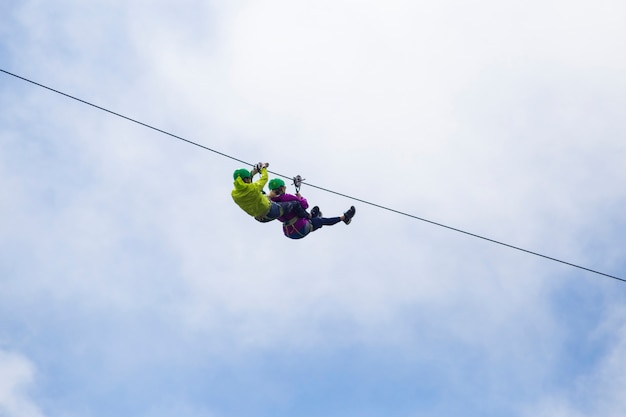 Adventurous tourist zip lining against cloudy sky