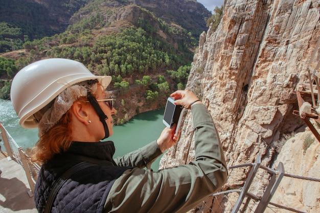 山探検で彼女の休暇に彼女の携帯電話で写真を撮るヘルメットを持つ冒険的な女性