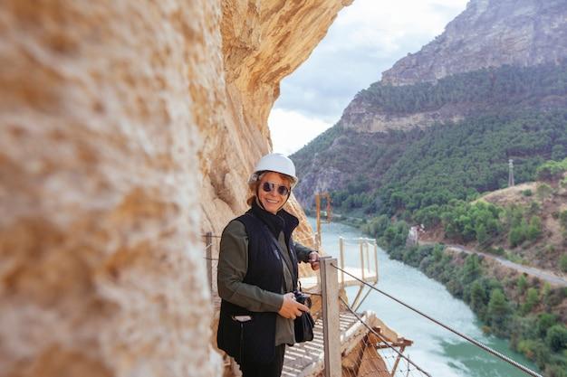 山の遠征で彼女の休暇に写真を撮るヘルメットを持つ冒険的な女性