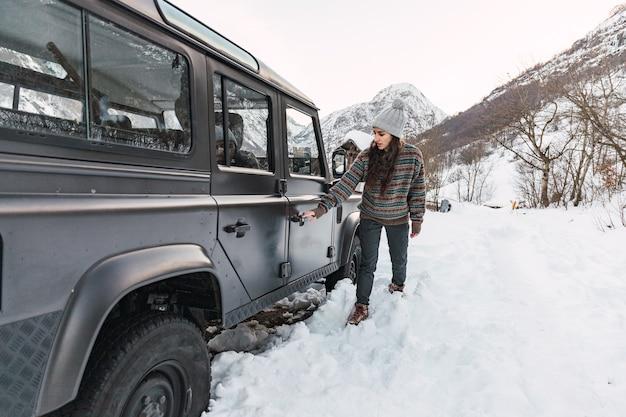 イタリア北部の雪に覆われたアルプスの山で彼女の車に入る冒険的な若い女の子。