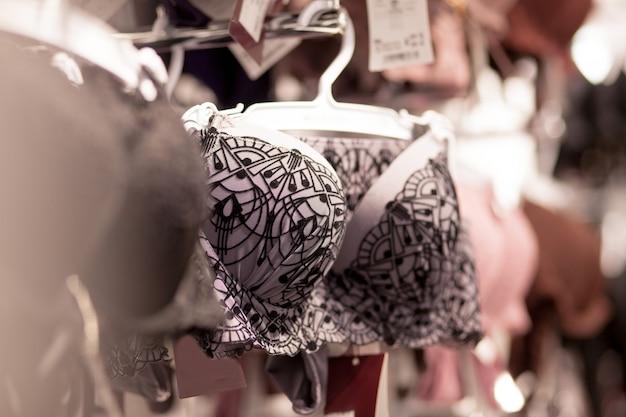 광고, 판매, 패션 개념 슈퍼마켓에서 옷걸이에 속옷을 선택하는 여자의 손 클로즈업