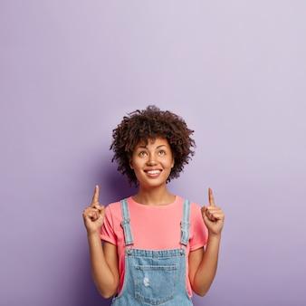 광고 및 홍보 개념. 위에 초점을 맞춘 사랑스러운 곱슬 머리 여자, 복사 공간에 두 검지 손가락을 가리키고, 위쪽으로 방향을 보여주고, 보라색 벽에 고립 된 세련된 옷을 입습니다.