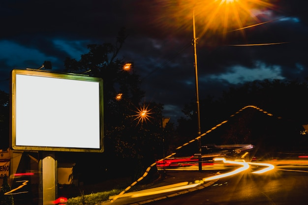 Advertisement billboard with blurred traffic lights at night