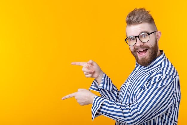 Концепция рекламы. забавный бородатый мужчина на желтом пространстве указывает на пустую копию пространства с