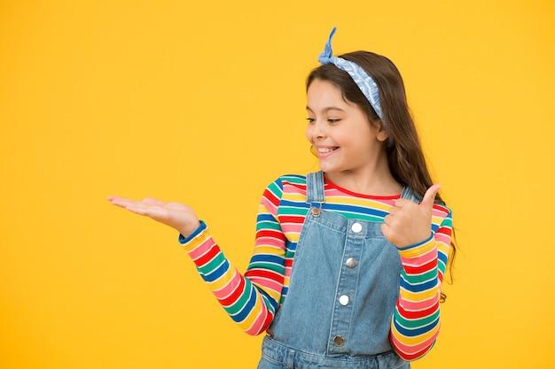광고 개념입니다. 어린이용 제품을 홍보합니다. 제품을 출시합니다. 제품 프레젠테이션. 아이의 행복한 웃는 얼굴은 열린 손바닥 복사 공간 노란색 배경에 무언가를 보여줍니다. 소녀는 제품을 보여줍니다.
