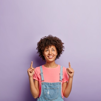 Advertisement and promotion concept. lovely curly haired woman focused above, points both index fingers on copy space, shows direction upwards, wears stylish outfit, isolated on purple wall