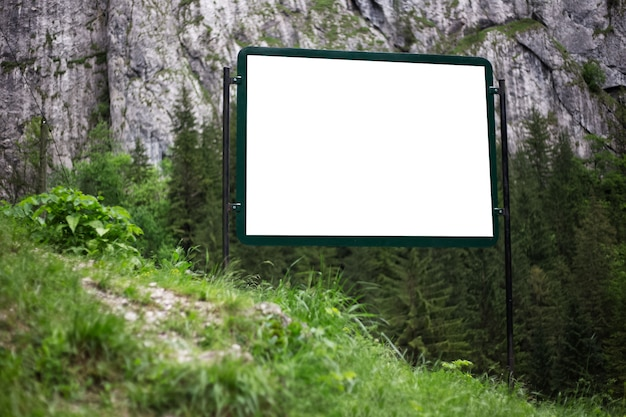 Advertising billboard with empty white mockup in green forest of mountains.